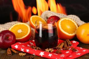Vin chaud parfumé en verre sur serviette sur fond de feu photo