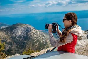 femme photographe avec voiture au sommet de la montagne