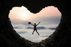 femme saute à l'intérieur de la grotte à la montagne