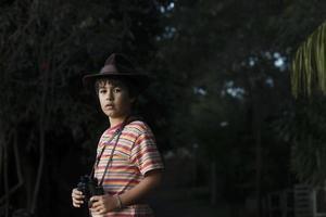 garçon avec chapeau aventurier regarder avec des jumelles.