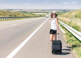 voyageur jolie fille souriante marche sur l'autoroute. photo