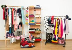 armoire avec des vêtements bien rangés et un bagage complet.