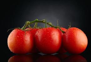 tomates rouges sur fond noir avec des gouttes d'eau