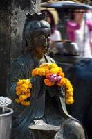 Statue de Bouddha en prière avec des soucis