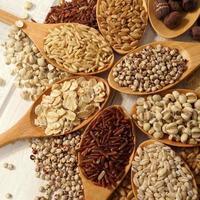 Céréales, haricots dans les cuillères sur table en bois blanc