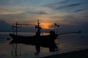 Bateau à longue queue silhouette avec puits de lumière du coucher du soleil photo