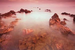 plage rocheuse au coucher du soleil.