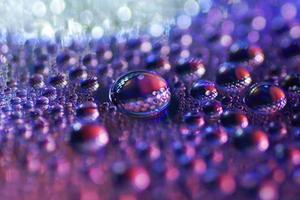Macro de gouttes d'eau sur une surface de DVD, lumière bokeh
