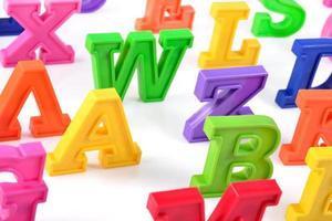 Lettres de l'alphabet coloré en plastique gros plan sur un blanc
