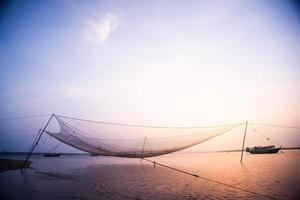 scène calme du filet de pêche contre le coucher du soleil violet.