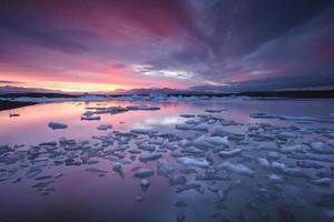 Icebergs flottant dans le lac glaciaire de fjallsarlon au coucher du soleil