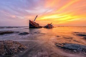 bateau de pêche échoué avec vue sur le coucher du soleil
