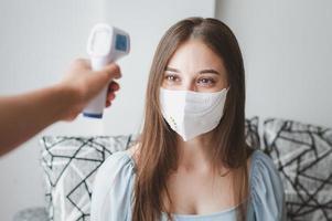 prendre la température de la femme au masque photo