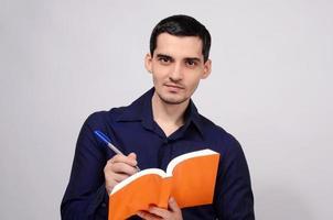 étudiant tenant un livre souriant. enseignant écrit sur cahier. photo