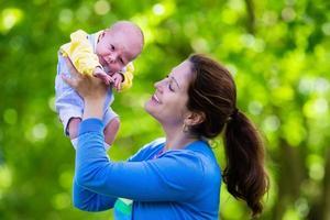 mère tenant bébé nouveau-né dans un parc photo
