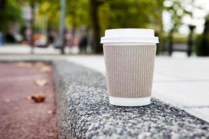 Tasse à café jetable sur trottoir avec ville en arrière-plan photo
