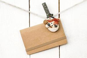 pinces à linge bonhomme de neige de Noël tenant une carte de voeux