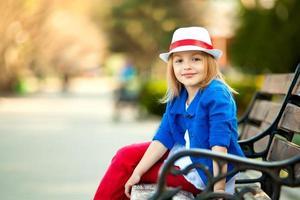 Portrait de petite fille sur un banc dans un parc
