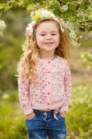 portrait de petite fille à l'extérieur dans un jardin luxuriant.