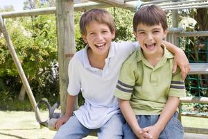 Deux jeunes amis masculins dans une aire de jeux en souriant photo