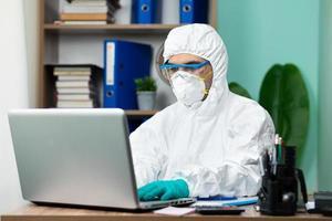 homme avec une suite de protection blanche travaillant sur un ordinateur portable