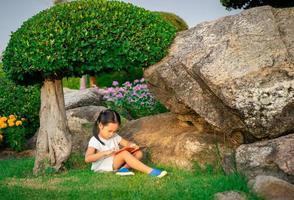 une petite fille mignonne en lisant un livre photo