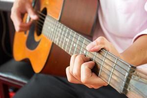 gros plan les mains de l'homme jouant de la guitare classique.