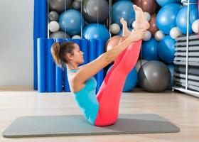 Exercice de culbuteur jambe ouverte Pilates sur tapis femme photo