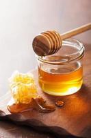 Louche en nid d'abeille et miel en pot sur fond de bois photo
