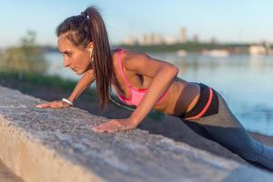 Fitness woman doing push ups entraînement en plein air soirée d'été photo
