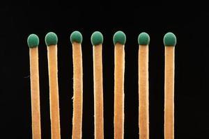 Ensemble de sept allumettes en bois vert isolé sur fond noir photo