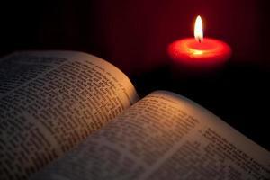 bible ouverte à la lumière de la bougie rouge - pentecôte photo