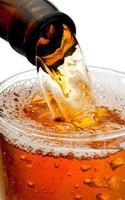 Verser de la bière de bouteille isolé sur fond blanc photo