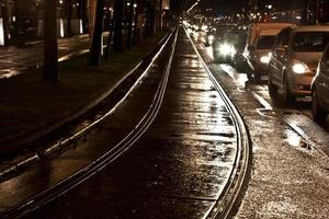 Les rails de chariot humides dans les rues réfléchissent la lumière