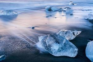 Belle glace bleue sur la plage de sable noir, Jokulsarlon, Islande