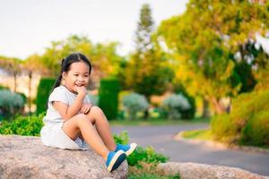 belle petite fille souriante assise à l'extérieur sur un gros rocher photo