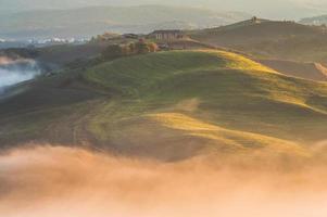 Matin brumeux dans le champ toscane éclairé beau lever de soleil