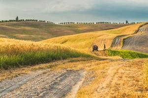 Tracteur avec une remorque sur les champs en Toscane, Italie photo