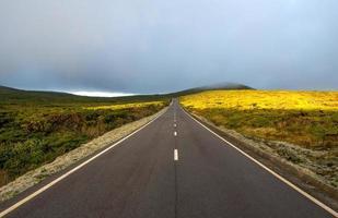 route entre collines avec nuages et soleil (Açores)