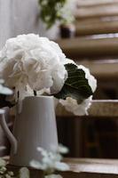 fleurs blanches dans un vase sur des marches en bois