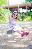 petite fille porte des lunettes de soleil sur une balançoire dans le parc