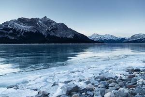photographie en niveaux de gris d'un plan d'eau et d'une montagne