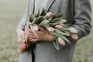personne tenant un bouquet de fleurs de tulipes