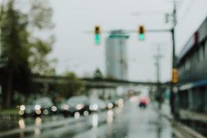 Voitures défocalisés à un feu de circulation un jour de pluie