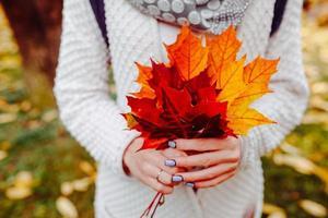 feuilles dautomne dans les mains de la fille photo