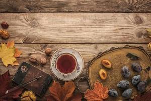 prunes, noix et feuilles avec cahier vintage et thé horizontal