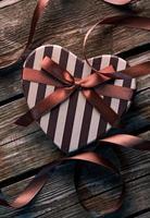 coffret cadeau Saint Valentin en forme de coeur sur des assiettes en bois.