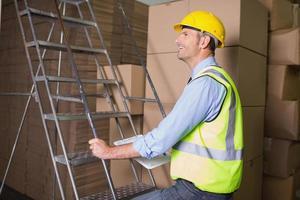 travailleur sur échelle dans l'entrepôt photo