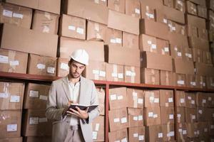 gestionnaire avec journal contre des boîtes dans l'entrepôt photo