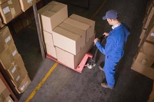 Travailleur poussant le chariot avec des boîtes en entrepôt photo